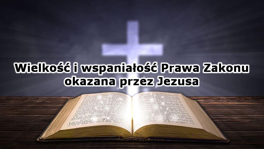 Na obrazku jest rozłożona na blacie stołu biblia, nad którą jaśnieje promieniejący krzyż zrobiony ze światła. Na środku jest napis: Wielkość i wspaniałość Prawa Zakonu okazana przez Jezusa